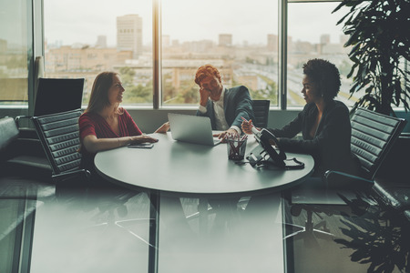 luxury room: Meeting of three businesspeople in luxury office room near window: group of three co-workers of different races are sitting at oval table and laughing at something, strong reflection in the bottom Stock Photo