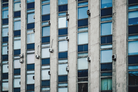 Texture of facade of building made in constructivism style with regular windows of nontrivial pattern and multiple outside air conditioning blocks, daytime, Moscow, Russia