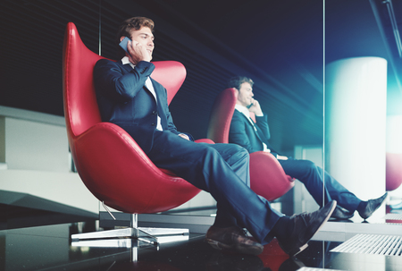 chillout: Smiling businessman in formal suit is sitting relaxed in chillout area of modern office interior on red curved armchair next to mirror and having phone conversation with his colleague