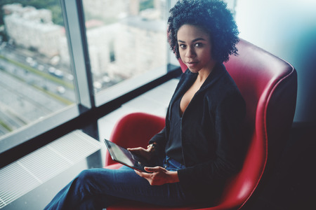 Charming young black businesswoman is sitting on red armchair next to window with highway in the background and holding digital tablet, office interior on high floor of skyscraper
