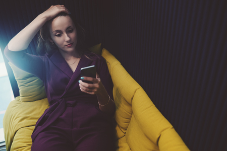 chillout: Tired beautiful caucasian businesswoman with headache is laying on fenced sofa in office chillout zone, holding her head with hand and having online conversation with her colleagues via smartphone