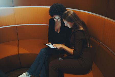 chillout: Two beautiful young businesswomen (caucasian one with long golden hair and Brazilian) are sitting on curved orange sofa in office chillout room and surfing internet via digital tablet Stock Photo