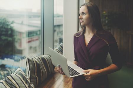Business lady em terno roxo está de pé em configurações de escritório ao lado da janela da área de relaxamento, segurando laptop e olhando para fora com área de espaço de cópia para anúncio, mensagem ou seu logotipo