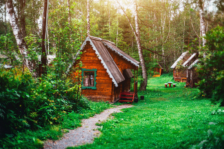 Small wooden house in tourist centre with fresh grass around and other houses in distance; green glade and paths to house of youth hostel surrounded by trees and located in forest of Altai district