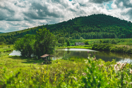 Summer landscape with small lake of fresh water, hills with forests in distance, green meadows of native grasses, arbour with trees near, submerged country house, Altai mountains, Aya district, Russia Stock Photo