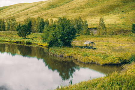 Abandoned summer alcove near beautiful pond�with calm water next to meadow with native grasses, trees and hills in distance; Altai mountains, Russia, Aya district