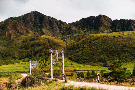 Rope bridge over the most narrow part of Katun river with mountain-ridge and green meadows in background and dirt road in foreground, Altai mountains, Kuyus district, Russia