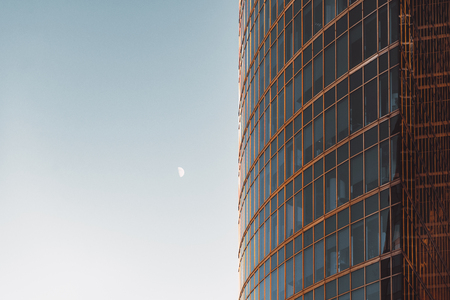 moon  metropolis: Side view of modern skyscraper teal and orange glassy facade with blue sky and on the other side, offices overlooked behind windows, Stock Photo
