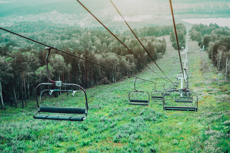 View from top of ropeway with multiple empty seats and stretched cables: green summer meadows and trees below, lake Monzherok and settlement of the same name in distance, Altai mountains, Russia