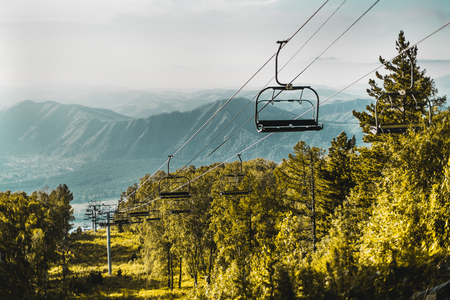 Landscape with cableway with empty seats stretching down over summer hills, meadow and trees of Altai mountains in Manzherok district with mountain ridge in background, Russia