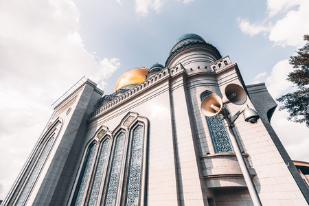 marmorate: Wide-angle view from bottom side of The Grand Cathedral Mosque made of white stone: golden dome and spires, loudspeaker for prayerful broadcasting and security camera in foreground, Moscow, Russia