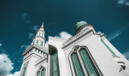 marmorate: Side view from bottom of beautiful Grand Cathedral Mosque made of stone: teal fancy facade and golden spires, quotation from Quran, sunny autumn day, Moscow, Russia