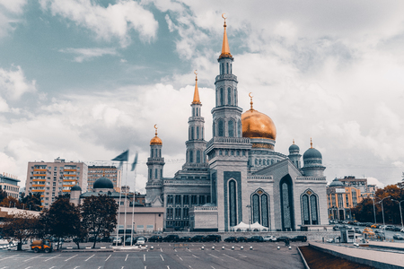 marmorate: Frontal view of The Grand Cathedral Mosque: bright golden domes and spires with crescents, ornamental facade, residential houses around, parking  with cars in foreground, Moscow, Russia Stock Photo
