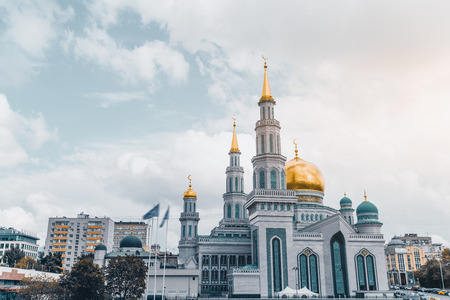 marmorate: Frontal view of beautiful Grand Cathedral Mosque: golden domes and spires with crescents, ornamental facade, residential houses around, parking with cars on the right, sunny day, Moscow, Russia Stock Photo