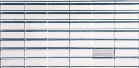 reflectivity: Modern bright regular glass and beams facade of contemporary building with one window of different reflectivity, metal construction behind, sunny day