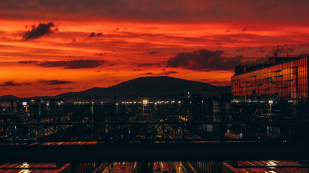 specular: Stunning sunset on huge railroad terminal with multiple railway tracks, glass facade on the right and hills ridge in distance; reddish sky, autumn evening, many reflections and lights, Adler, Russia