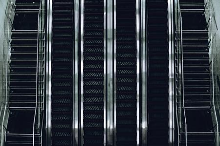 Vista superior da linha de escada rolante de vidro e cromo contemporânea de quatro trilhos com duas escadas de ambos os lados no terminal do aeroporto, deport ou construção de mall moderno, especular metálico forte