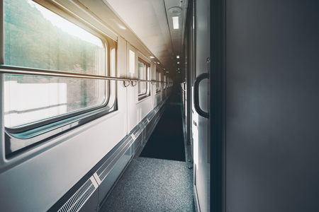 stateroom: Wide-angle shooting of long and empty double-decker passenger train interior with multiple closed doors of compartments, hills outside the windows, carpet on the floor, railings on the walls