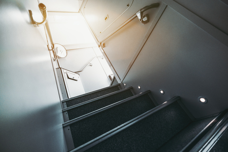 stateroom: Wide-angle view from bottom of modern staircase with floor illumination going up to second floor of two-storey contemporary passenger train; railing on both sides, dustbin and mirror in a distance