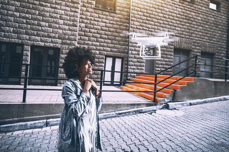Beautiful cheerful young biracial curly lady posing in front of mobile camera of flying drone in urban settings while making online report for subscribers of her video channel
