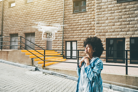Smiling cute black girl is recording her video blog using modern flying drone: she is standing in the center of urban street and looking up into camera of quadrupter with facade of building behind Stock Photo
