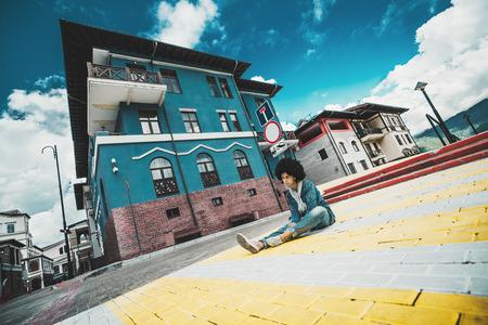 Vista granangular de la muchacha negra pensativa que se sienta en las piedras de pavimentación a la derecha en el paso de peatones de la calle urbana en día soleado del otoño con los edificios del centro turístico en el fondo, distrito de Estosadok, Sochi, Rusia Foto de archivo - 87332585