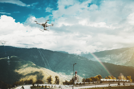 Modern drone is rushing to explore beautiful iris stretching over the hills on a sunny day with small rain; contemporary white quadrupter is shooting on video camera stunning rainbow over mountains Stock Photo
