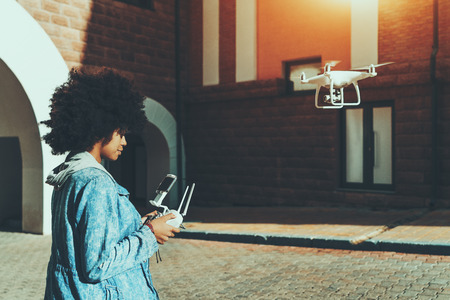Young beautiful African American woman standing on pavement in urban settings and remotely tuning camera of flying drone in front of her, preparing to record report for subscribers of her video blog