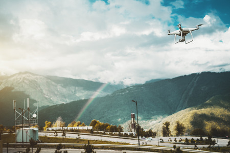 View of contemporary drone which is flying to capture on video of beautiful rainbow stretching between overgrown mountains in the background on sunny autumn day with small rain through sunshine Banco de Imagens