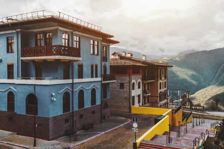 View of empty and neat streets of a small resort town on rain through sunshine with colorful hotels, inns, and walls; overgrown mountains in background with low clouds, district of Sochi, Russia Banco de Imagens