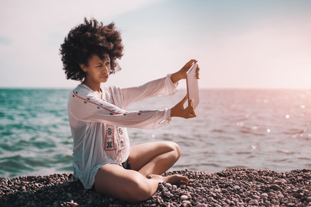 Curly African American girl in wet chemise is taking selfie via her digital tablet while sitting on pebble nearshore on sunny summer day with clear sky and teal water in defocused background