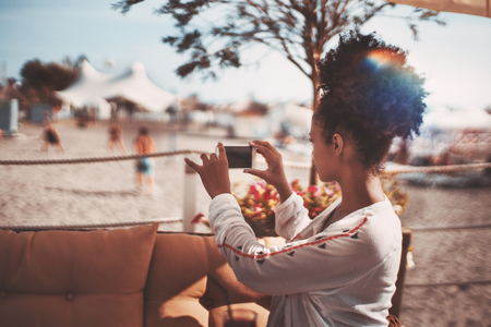 repose: Young black woman is photographing beach with people playing volleyball in defocused background; mixed female is using her smartphone to take video of men playing football on the sand of resort beach