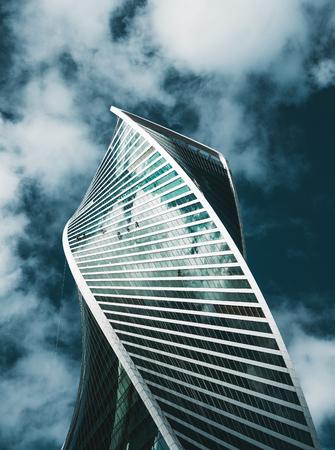 Vista do fundo do moderno arranha-céu torcido refletindo as nuvens em sua fachada de vidro, com vários montanhistas industriais lavando suas janelas; construindo a partir de