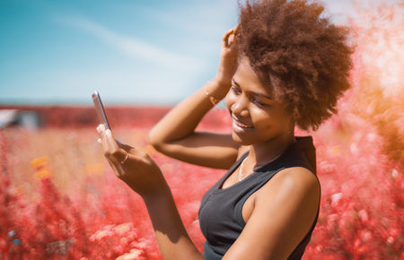 Beautiful cheerful young African American female is fixing her curly hair using frontal camera of cell phone as a mirror; vivid red colors in defocused background, shallow depth of field Stock Photo