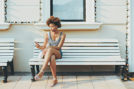 Charming young black girl is sending online message via smartphone while sitting on street bench with facade building behind her with copy space zone for text, your advert or other information Foto de archivo