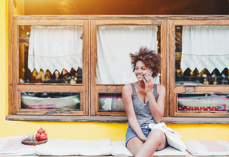 Laughing cute Brazilian girl speaking on smartphone while sitting on cushion in front of yellow wall and window; young smiling African American female with cellphone waiting friend in street cafe Foto de archivo