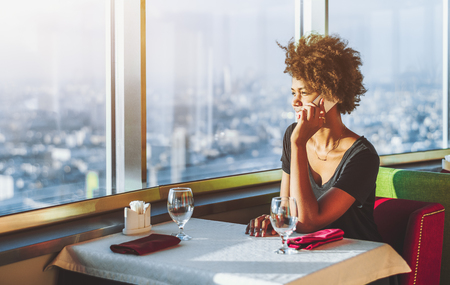 Charming pensive young black female is sitting at the table of modern luxury restaurant located on top of tower and speaking on the phone; with cityscape below outside the window in blurred background