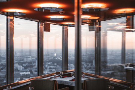 Dark abstract interior of modern luxury restaurant or cafe with multiple reflections, red ceiling, and oval lamps on it, panoramic windows with cityscape from very high point in defocused background