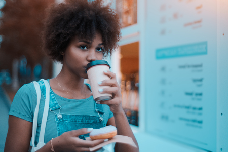 Young cute Brazilian girl with curly afro hair in jean overalls and striped t-shirt is standing near food kiosk on late evening, drinking coffee from paper cup and holding delicious donut ready to eat Foto de archivo