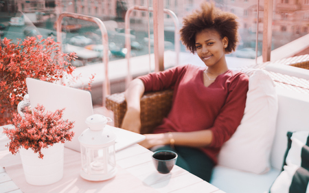 True tilt-shift view of cute young black female freelancer sitting in bright street bar located on the roof of building with cup of tea and laptop; vivid reddish colors; sunny summer day Foto de archivo