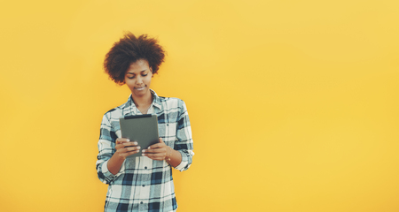 Serious young African American student female in front of yellow solid wall with digital tablet; beautiful pensive black teenage girl in checkered shirt using digital pad on isolated lemon background