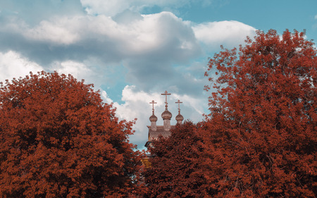 Carved wooden orthodox church cupola with crosses partly closed by trees of vivid unnatural reddish colors in foreground; cloudy sky in the background, overcast summer day, Moscow, Russia