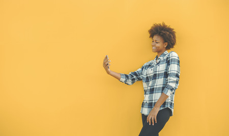 Portrait on isolated yellow solid color of beautiful young smiling curly student girl in shirt taking selfie on camera of her cell telephone; with copy space place for logo, your text or advertising Foto de archivo