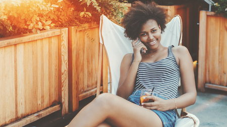 Charming smiling young black woman outdoor with glass of beverage talking with boyfriend via smartphone; cheerful Brazilian girl in striped t-shirt sitting in street bar and having phone conversation