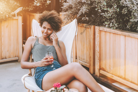 Cute black girl with afro hair is having phone conversation while sitting in street bar with glass of spritz beverage; young beautiful African American female in cafe outdoor talking on the smartphone Stock Photo