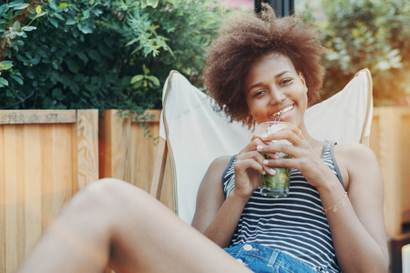 Laughing charming young black girl in jean shorts and striped t-shirt is holding a glass of cold delicious mojito beverage while chilling on the deck chair outdoor in street bar or cafe
