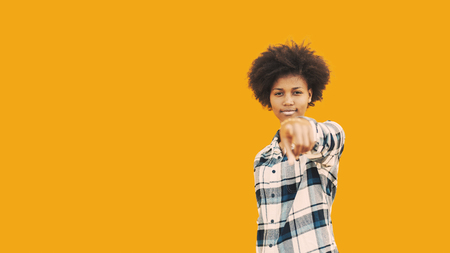 Portrait of beautiful self-confident black student girl standing in front of isolated yellow solid background and pointing with her finger on camera; with copy space zone for advertising text or logo