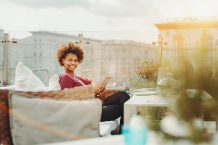 Mulher jovem e negra negra alegre que usa tableta digital enquanto est