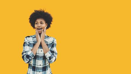 Jovem estudante adolescente negra na camisa xadrez em frente ao fundo isolado amarelo sólido está sentindo surpresa alegre com as mãos para enfrentar; com espaço de cópia para anúncio, texto ou seu logotipo
