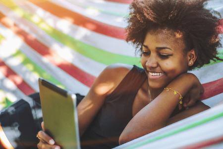 Adolescente alegre feminino brasileiro com cabelos africanos está deitado em uma rede colorida de lanchas, localizado em um parque público no caloroso dia ensolarado e sorrindo ao ler memes engraçados em seu tablet digital